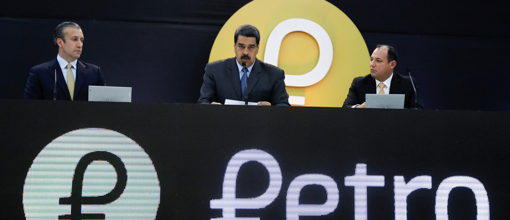 "Venezuela's President Nicolas Maduro (C) speaks during the event launching the new Venezuelan cryptocurrency ""Petro"", next to Venezuela's Vice President Tareck El Aissami (L) and the Minister for University Education, Science and Technology Hugbel Roa, in Caracas, Venezuela February 20, 2018. REUTERS/Marco Bello - RC1DB8D4BDC0"