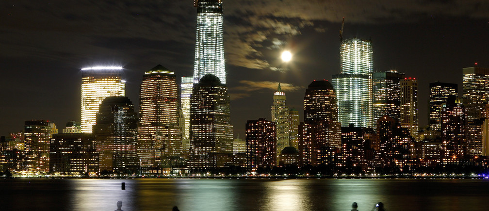 The moon rises behind the skyline of New York's Lower Manhattan and One World Trade Center as people stand along the Hudson River in Jersey City, New Jersey, October 1, 2012.
