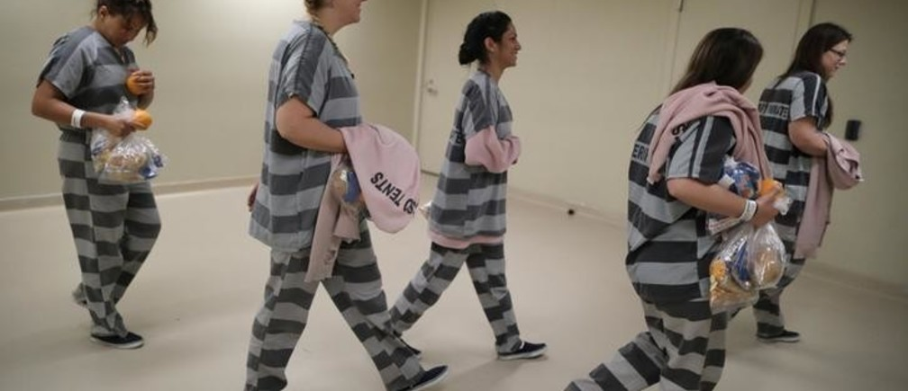 """Female inmates walk from their holding cell to the MCSO Animal Safe Haven (MASH) Unit in a former jail that has become a shelter for abused and neglected animals seized in Maricopa County Sheriff's Office investigations, in Phoenix, Arizona, U.S., April 25, 2017. REUTERS/Lucy Nicholson  SEARCH """"DOGS NICHOLSON"""" FOR THIS STORY. SEARCH """"WIDER IMAGE"""" FOR ALL STORIES."""