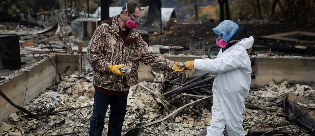 Vanthy Bizzle hands some small religious figurines to her husband Brett Bizzle in the remains of their home after returning for the first time since the Camp Fire forced them to evacuate in Paradise, California, U.S. November 22, 2018.  REUTERS/Elijah Nouvelage - RC1C3BA983B0
