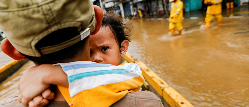 A girl is carried by her father across floodwaters in the Jatinegara area after heavy rains in Jakarta, Indonesia, January 2, 2020.