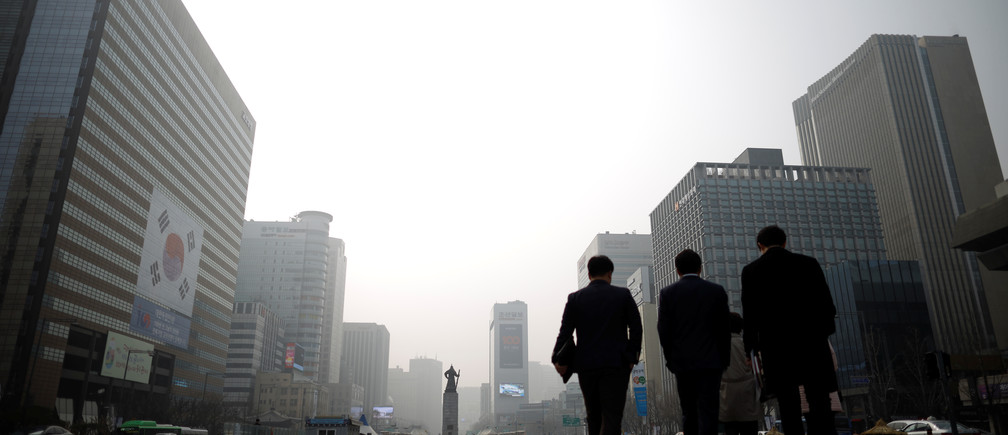 Businessmen walk during a polluted day in Seoul, South Korea, March 5, 2019.   REUTERS/Kim Hong-Ji - RC149131EF50