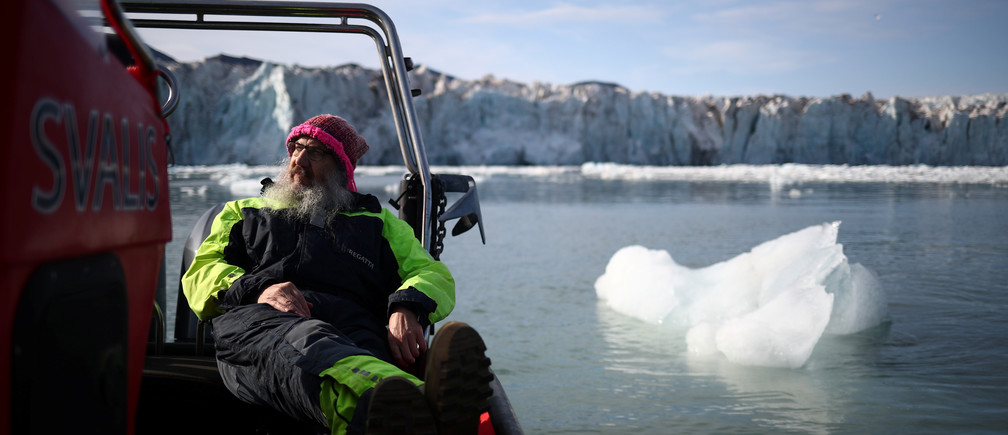 "International director of the Norwegian Polar Institute, Kim Holmen, relaxes with a cup of tea as he travels past the Wahlenberg Glacier in Oscar II land at Spitsbergen in Svalbard, Norway, August 5, 2019. Holmen has lived in the northern Norwegian archipelago of Svalbard for three decades. He describes the changes he's seen as ""profound, large and rapid."" ""We are losing the Svalbard we know. We are losing the Arctic as we know it because of climate change,"" he said. ""This is a forewarning of all the hardship and problems that will spread around the planet."" REUTERS/Hannah McKay      SEARCH ""SVALBARD CLIMATE"" FOR THIS STORY. SEARCH ""WIDER IMAGE"" FOR ALL STORIES. - RC12AB368890"