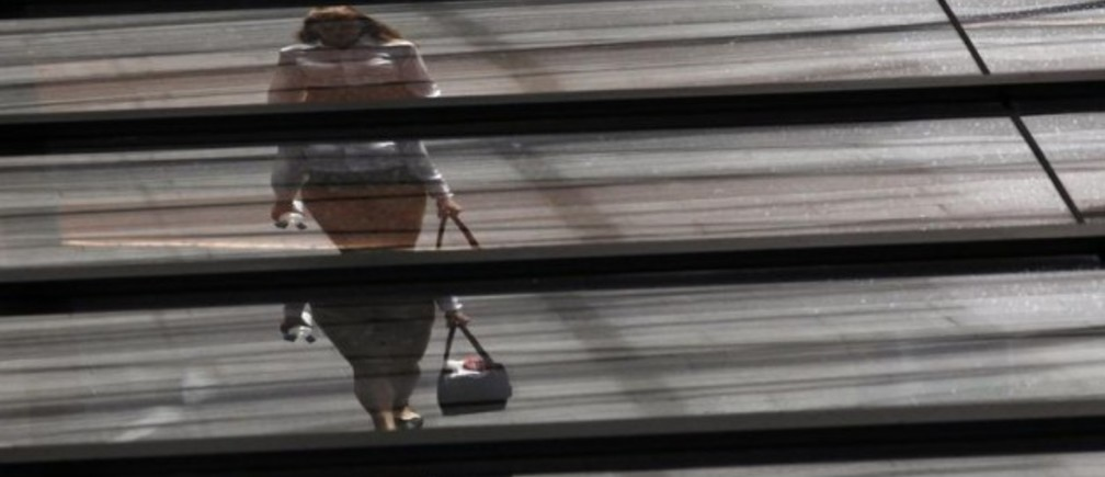 Image: An office worker is reflected on the roof of a building. REUTERS/Daniel Munoz