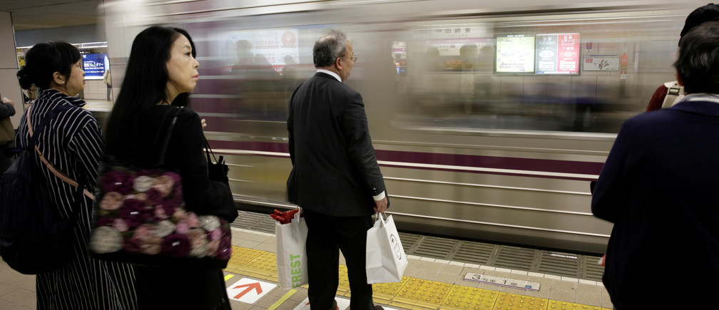Commuters and an office worker wait for a train in Osaka, western Japan October 24, 2017.   Picture taken October 24, 2017.    REUTERS/Thomas White             GLOBAL BUSINESS WEEK AHEAD      SEARCH GLOBAL BUSINESS 30 OCT FOR ALL IMAGES - RC136F687FF0