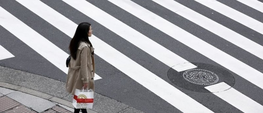 A woman holds a shopping bag as she waits at a pedestrian crossing in the Ginza district in Tokyo, Japan, March 24, 2016.  Japan's consumer inflation was flat in the year to February as low energy costs and weak consumption put a lid on price growth, keeping the central bank under pressure to top up stimulus even after easing policy less than two months ago. REUTERS/Thomas Peter - GF10000359754