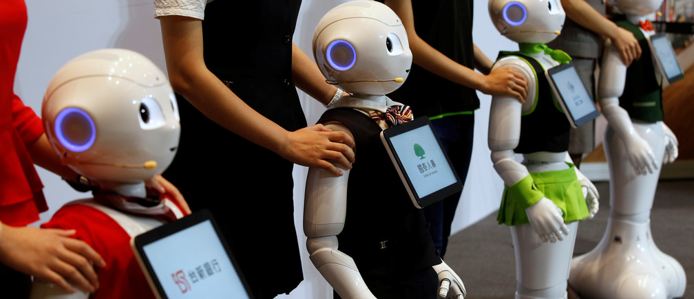 SoftBank's robots 'pepper', dressed in different bank uniforms, are displayed during a news conference in Taipei, Taiwan July 25, 2016. REUTERS/Tyrone Siu - D1BETROXIJAA