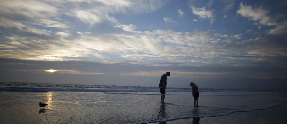 A man and a girl paddle in the Pacific Ocean at sunset in Santa Monica, California February 5, 2015.