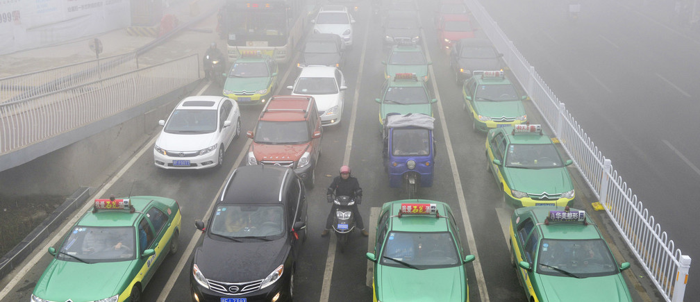 An electric bicycle stops among cars while waiting at a traffic light on a hazy day in Xiangyang, Hubei province January 16, 2015. Picture taken January 16, 2015. REUTERS/Stringer (CHINA - Tags: ENVIRONMENT TRANSPORT) CHINA OUT. NO COMMERCIAL OR EDITORIAL SALES IN CHINA - GM1EB1H0UXY01