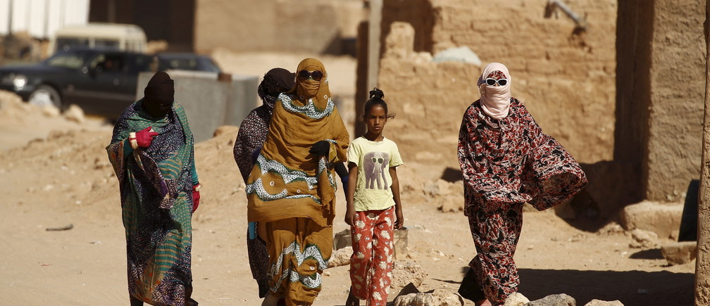 """Indigenous Sahrawi women walk through Al Smara desert refugee camp in Tindouf, southern Algeria March 4, 2016. In refugee camps near the town of Tindouf in arid southern Algeria, conditions are hard for indigenous Sahrawi residents. Residents use car batteries for electricity at night and depend on humanitarian aid to get by. The five camps near Tindouf are home to an estimated 165,000 Sahrawi refugees from the disputed region of Western Sahara, according to the United Nations refugee agency UNHCR. REUTERS/Zohra Bensemra SEARCH """"THE WIDER IMAGE"""" FOR ALL STORIES  Matching text ALGERIA-SAHARA/ - RTS9CD3"""