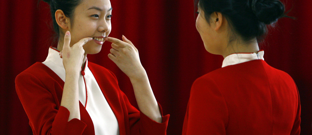 A student shows another how to smile during an etiquette training class at a vocational school in Beijing January 7, 2008. A small group of vocational students, mostly between the ages of 16 and 18, are going through physical conditioning as well as professional training for dressing and etiquette in order to be stewards for the service industry, but a select few will become stewards for medal ceremonies during the 2008 Beijing Olympics.  REUTERS/David Gray   (CHINA) - RTX5ATW