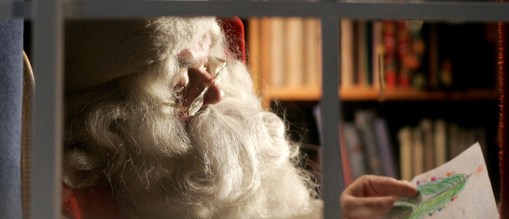 A man dressed as Santa Claus reads letters from children from around the world in his office at  the Santa Claus' Village at the Arctic Circle near Rovaniemi, Finland. Picture taken December 18, 2007. REUTERS/Kacper Pempel(FINLAND) - GM1DWVTLDAAA