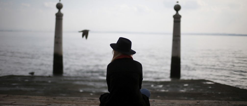 A woman rests at the Cais das Colunas in front of the Tagus River in downtown Lisbon, Portugal November 16, 2015.