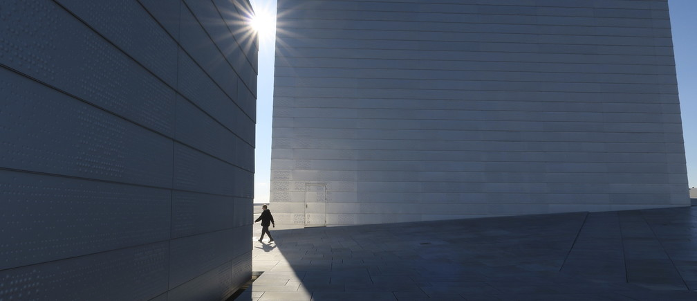 A man walks between two structures that form part of the roof of the Oslo Opera House, in Oslo, Norway, October 15, 2015. REUTERS/Russell Boyce      TPX IMAGES OF THE DAY      - GF10000246185