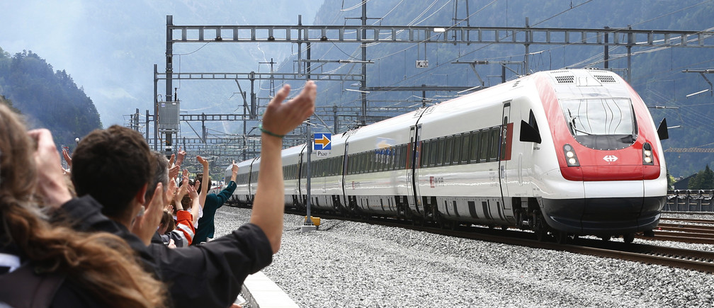 Guests waves at a train that has crossed the tunnel during the opening ceremony of the NEAT Gotthard Base Tunnel, the world's longest and deepest rail tunnel, near the town of Erstfeld, Switzerland June 1, 2016.  The 57.1-km (35.5 mile)-long Gotthard Base Tunnel, 17 years under construction and designed to last a century, is part of a 23 billion Swiss franc (23.1 billion USD) infrastructure project to speed passengers and cargo by rail below the Alps, as much as 2.3 km (1.7 miles) under the mountain chain, that divides Europe's north and south.  REUTERS/Arnd Wiegmann - RTX2F4E5