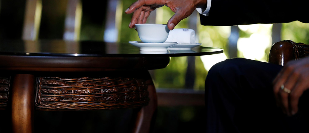 U.S. President Barack Obama reaches for his tea cup as he drinks tea with Chinese President Xi Jinping at a pavillion, at West Lake State Guest House in Hangzhou, in eastern China's Zhejiang province, September 3, 2016. REUTERS/Carolyn Kaster/Pool - RTX2NZY4