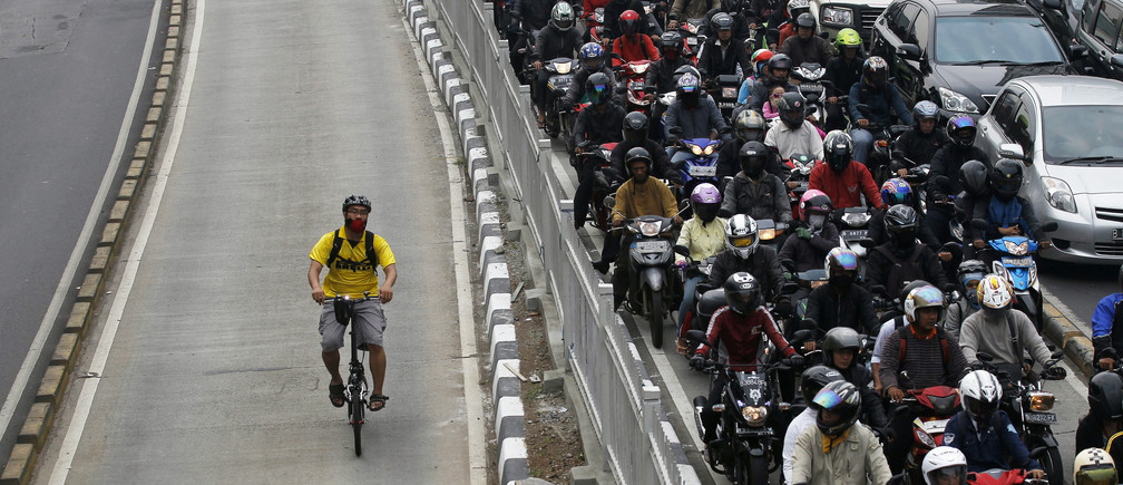 A man rides a bicycle in a bus lane next to a morning rush hour traffic jam in Jakarta November 10, 2011. Indonesia's central bank said on Thursday it saw economic growth in 2012 could slow to below 6.5 percent, as it cut its benchmark overnight interest rate by a surprise 50 basis points to a record low 6 percent to ward off the effect of a slowdown in Europe and China. environment renewable solar energy change transition friendly environment carbon footprint carbon emissions reduction change natural climate change global warming air pollution clean energy power renewables plastic plastics