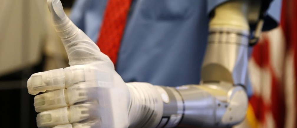 Vietnam veteran Fred Downs gives a thumbs up during a demonstration of modular prosthetic arm technology developed by the Defense Advanced Research Projects Agency (DARPA) at the Pentagon in Washington April 22, 2014.