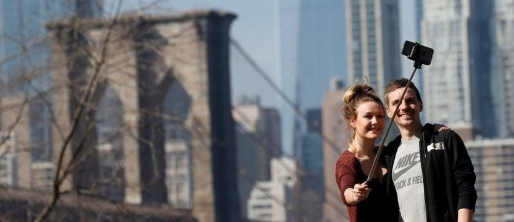 A couple pose for a selfie with the Brooklyn Bridge in the distance during unseasonably warm weather in Brooklyn, New York, U.S., February 21, 2018. REUTERS/Brendan McDermid - RC18DD4E03E0