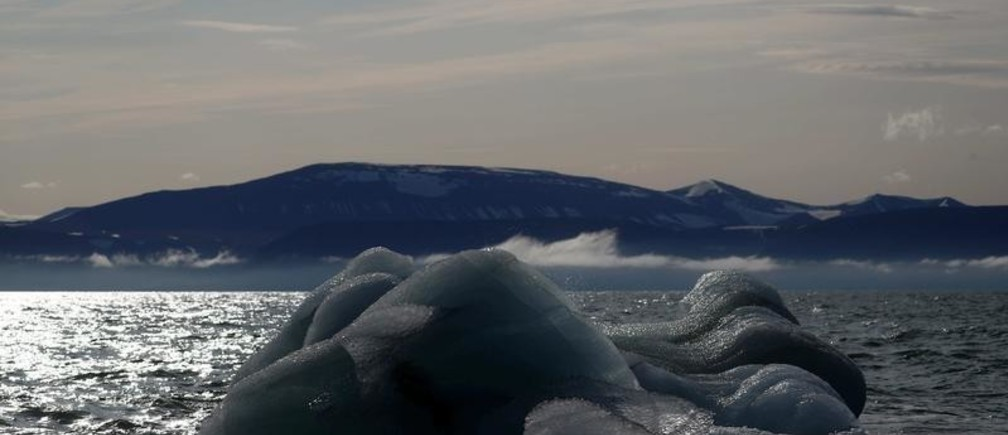 """An iceberg floats near the Wahlenberg Glacier in Oscar II land at Spitsbergen in Svalbard, Norway, August 5, 2019. REUTERS/Hannah McKay   SEARCH """"SVALBARD CLIMATE"""" FOR THIS STORY. SEARCH """"WIDER IMAGE"""" FOR ALL STORIES. - RC15C5685FD0"""