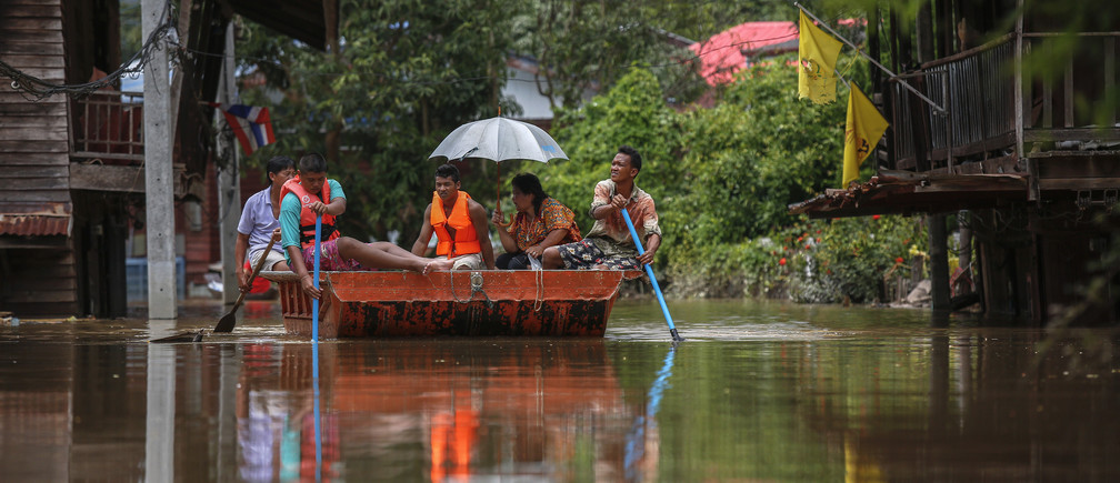People paddle along a flooded street in Prachinburi, Thailand, in 2013.