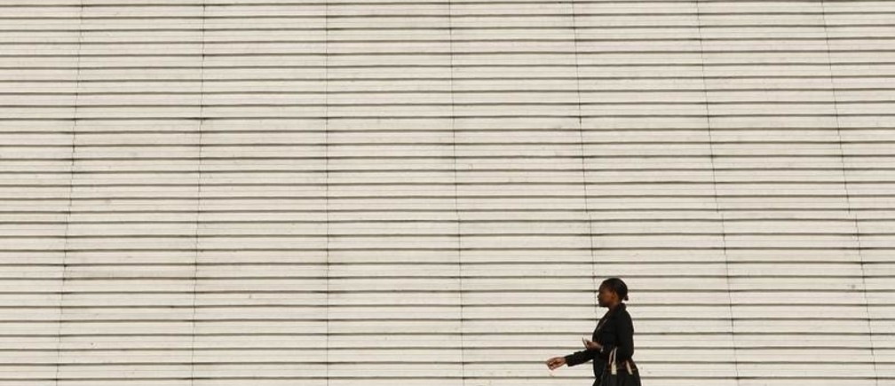 A businesswoman walks past the steps at the Arche de la Defense, the financial and business district west of Paris, August 5, 2009. REUTERS/Benoit Tessier (FRANCE BUSINESS) - PM1E585199001