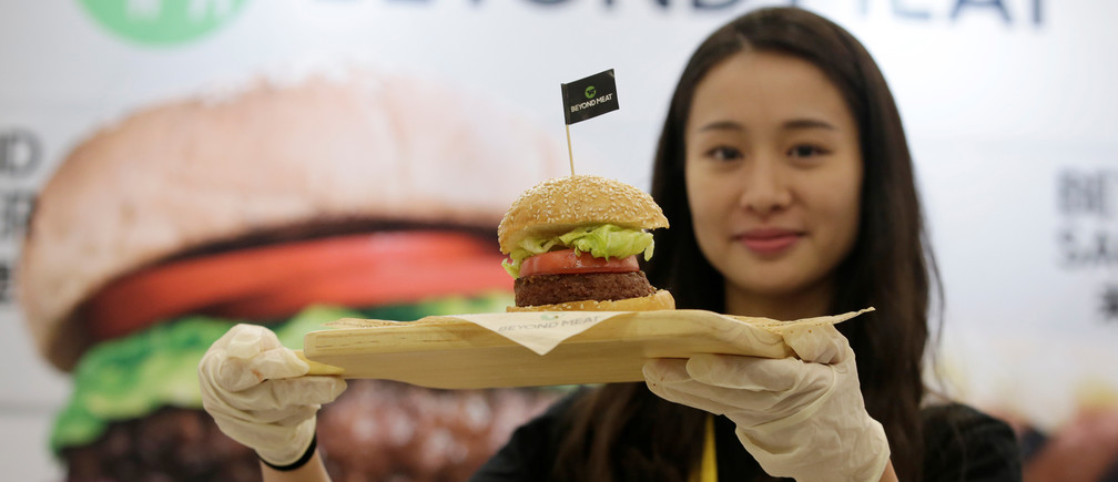 A staff member displays a burger with a Beyond Meat plant-based patty at VeggieWorld fair in Beijing, China November 8, 2019. Picture taken November 8, 2019. REUTERS/Jason Lee - RC2YDD9MVMC3