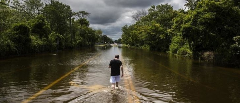 A man walks down a flooded road in Islip, New York August 13, 2014. More than a foot of rain hit parts of New York's Long Island on Wednesday, enough to set a preliminary state record, triggering flash floods and swamping cars on major roads that were turned into rivers during the morning rush hour. REUTERS/Lucas Jackson (UNITED STATES - Tags: ENVIRONMENT DISASTER TPX IMAGES OF THE DAY)