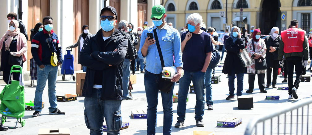 People wearing protective face masks queue at Porta Palazzo market in Turin after it reopened with social distancing rules as Italy begins a staged end to a nationwide lockdown, following the outbreak of the coronavirus disease (COVID-19), Turin, Italy, May 4, 2020. REUTERS/Massimo Pinca - RC2NHG9RD43Y