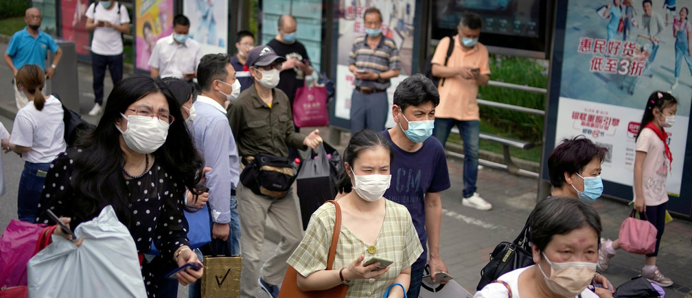 People wearing protective face masks are seen on a street following an outbreak of the novel coronavirus disease (COVID-19), in Shanghai, China May 28, 2020. REUTERS/Aly Song - RC2MXG94W2IE