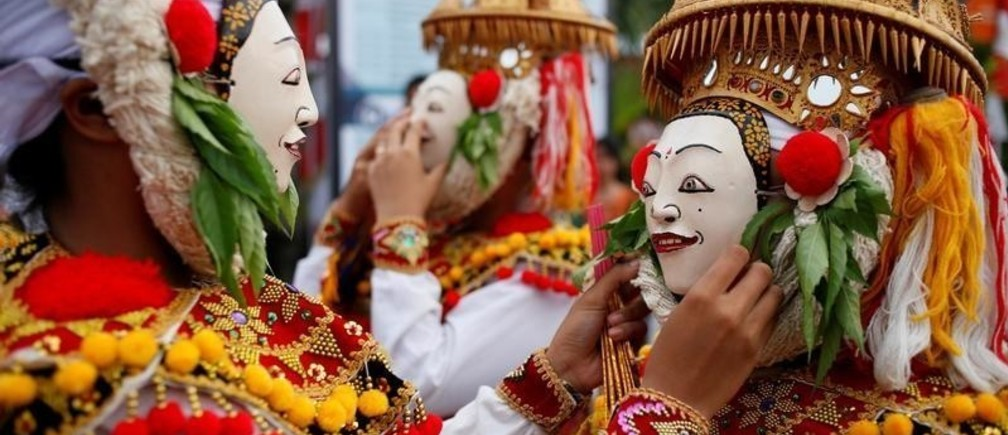 Balinese Hindus wear masks as they prepare before performing sacred Telek dance at a festival in Klungkung, Bali, Indonesia, April 28, 2019. REUTERS/Johannes Christo - RC1469805500