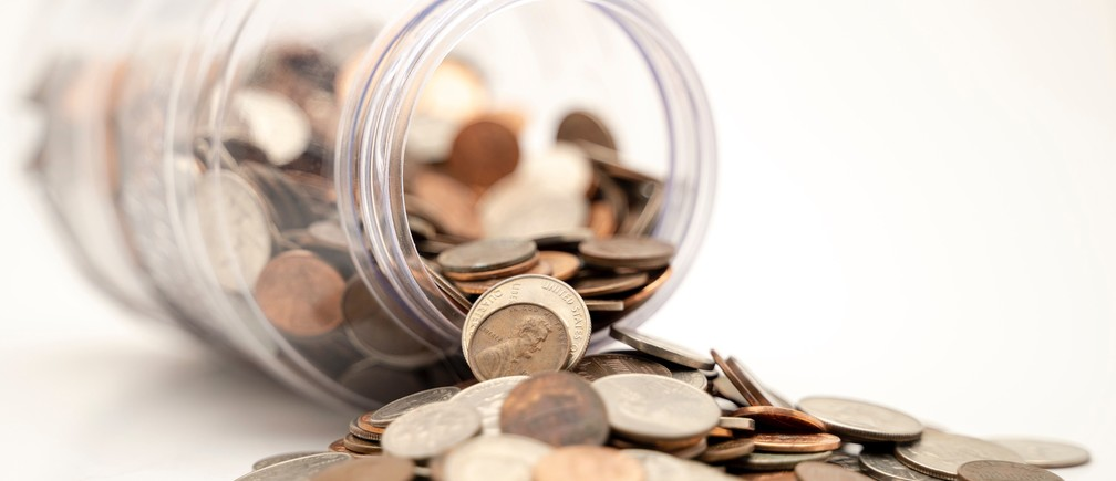 Pennies fall out of a jar.