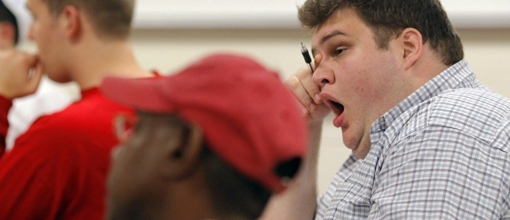 "A student yawns during the ""Fundamentals of Algebra"" class, which is held from 11:45pm to 2:30am, at Bunker Hill Community College in Boston, Massachusetts September 8, 2010, one of five midnight classes offered this semester due to surging enrollment. Bunker Hill's experiment with ""midnight oil"" classes began with two classes a year ago and a handful of other colleges, from Maryland to Illinois to California, have followed Bunker Hill's lead and are offering midnight classes to cope with overflowing enrollment. Picture taken September 8, 2010.  REUTERS/Brian Snyder    (UNITED STATES - Tags: EDUCATION SOCIETY) - RTXSS3F"