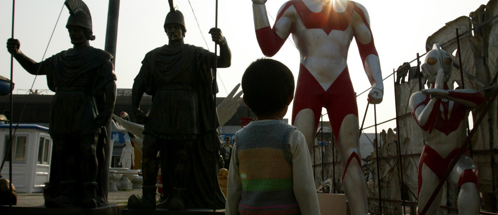 A child looks at an Ultraman, a Japanese science fiction superhero,being displayed beside Roman warriors figures at a moulding factory inGuangzhou, capital of China's Guangdong province, February 11, 2003.Symbols of different cultures stand side by side as manufacturersdevelop the figures world-wide exportation. China's exports rose anannual 18.3 percent to around $315 billion in 2002. Picture takenFebruary 11, 2003. REUTERS/Bobby YipBY/PB - RP3DRINAHRAA