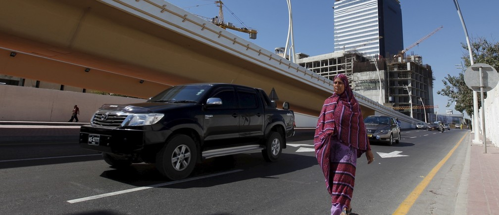 The construction site of the Bharia Icon 62 story building is seen in the background as a woman walks along a street in Karachi, Pakistan, February 9, 2016.