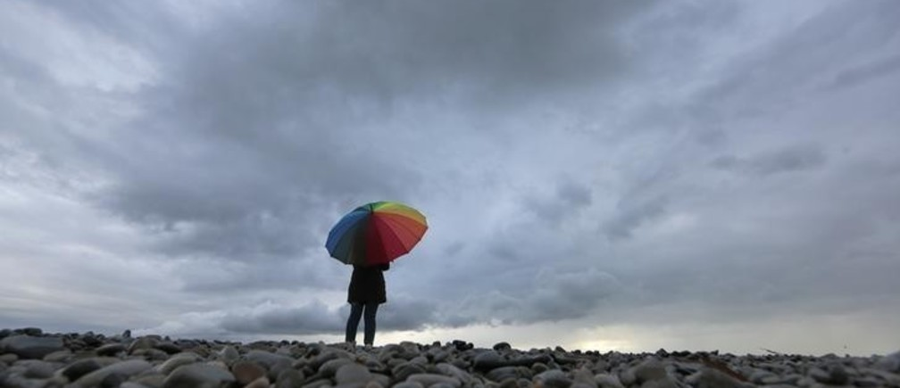 A woman protects herself under an umbrella on the beach in Nice while heavy rain and storm hit southeastern France November 15, 2014. REUTERS/Eric Gaillard (FRANCE - Tags: ENVIRONMENT)