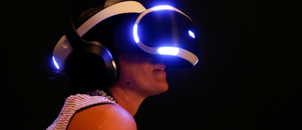 A woman tries on earphones and a headset used for virtual reality at the Venice Virtual Reality a competition during 74th Venice Film Festival in Venice, Italy, August 29, 2017. REUTERS/Alessandro Bianchi - RC12FC8D50B0
