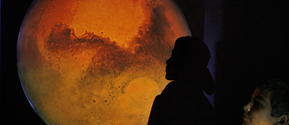 A Jordanian boy poses with an image of Mars projected on a wall during a gathering to watch the red planet in Amman's sky January 28, 2010.   REUTERS/Ali Jarekji   (JORDAN - Tags: SCI TECH) - GM1E61T0AYQ01