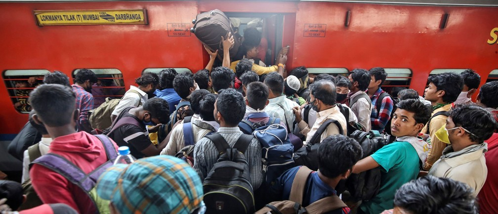 Migrant workers and their families board an overcrowded passenger train, after government imposed restrictions on public gatherings in attempts to prevent spread of coronavirus disease (COVID-19), in Mumbai, India, March 21, 2020. REUTERS/Prashant Waydande - RC28OF984OPS