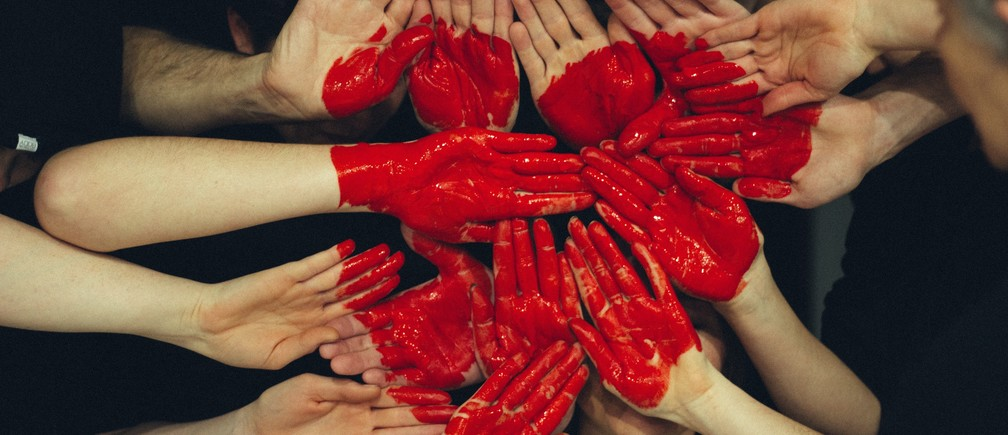 Hands painted red to form a heart shape