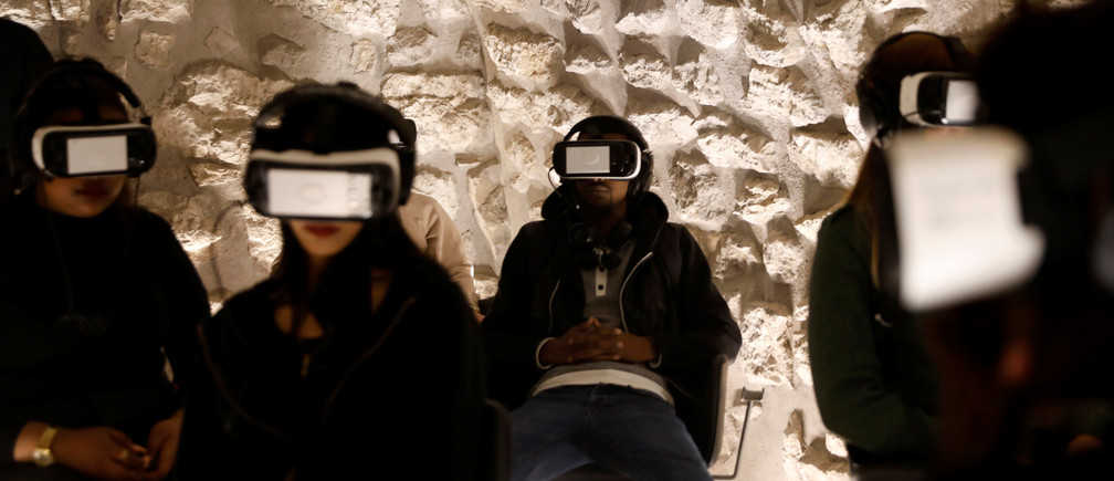 Visitors wear headsets as they experience a virtual reality tour depicting Jerusalem as it was two millennia ago, at a visitors center near some of the world's most sacred sites holy to Jews, Muslims and Christians, in Jerusalem's Old City February 20, 2017. Picture taken February 20, 2017. REUTERS/Ronen Zvulun - RTSZTCV
