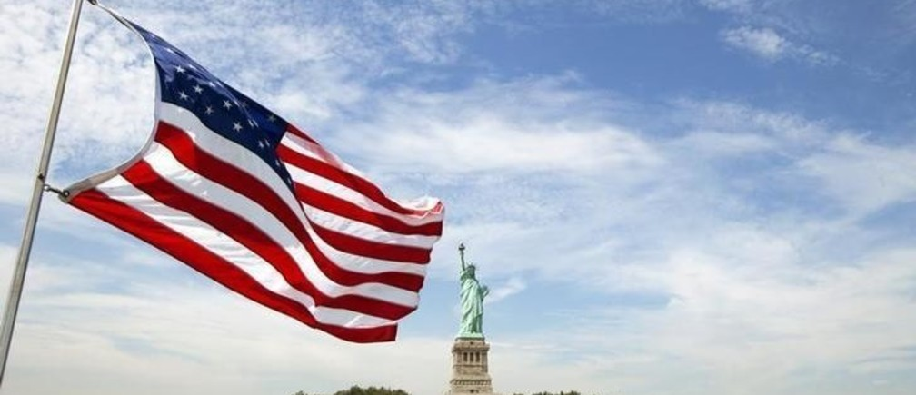 An U.S. flag waves in the wind on a boat near the Statue of Liberty in New York August 31, 2011.  REUTERS/Lucas Jackson (UNITED STATES - Tags: CITYSPACE)