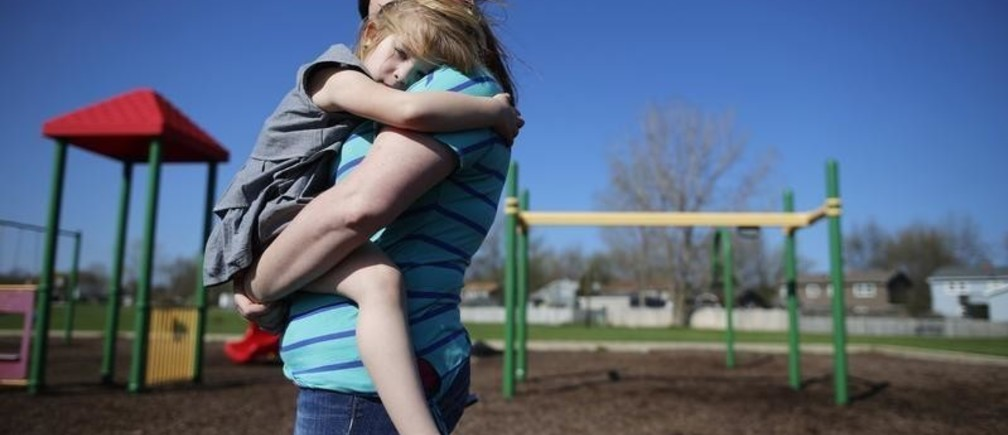 Andrea Smith holds her daughter Norah at a playground in Winthrop Harbor, Illinois, May 9, 2014. Three of her children have been diagnosed with atypical Hemolytic Uremic Syndrome, and one is a carrier which was diagnosed using genome sequencing. Once strictly the domain of research labs, gene-sequencing tests increasingly are being used to help understand the genetic causes of rare disease, putting insurance companies in the position of deciding whether to pay the $5,000 to $17,000 for the tests. Genetics experts say that sequencing more than doubles the chances that families get a diagnosis, and saves spending on multiple tests of single genes. Even if no treatment is found, the tests can also end hugely expensive medical odysseys as parents frantically search for the cause of their child's furtive illness. Picture taken May 9, 2014. To match Insight HEALTH-SEQUENCING/    REUTERS/Jim Young (UNITED STATES - Tags: SCIENCE TECHNOLOGY HEALTH SOCIETY BUSINESS) - GM1EA6J1M9N01