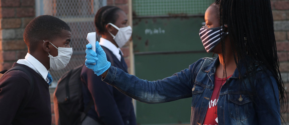 A teacher screens students as schools begin to reopen after the coronavirus disease (COVID-19) lockdown in Langa township in Cape Town, South Africa June 8, 2020. REUTERS/Mike Hutchings - RC2X4H9TF0WI