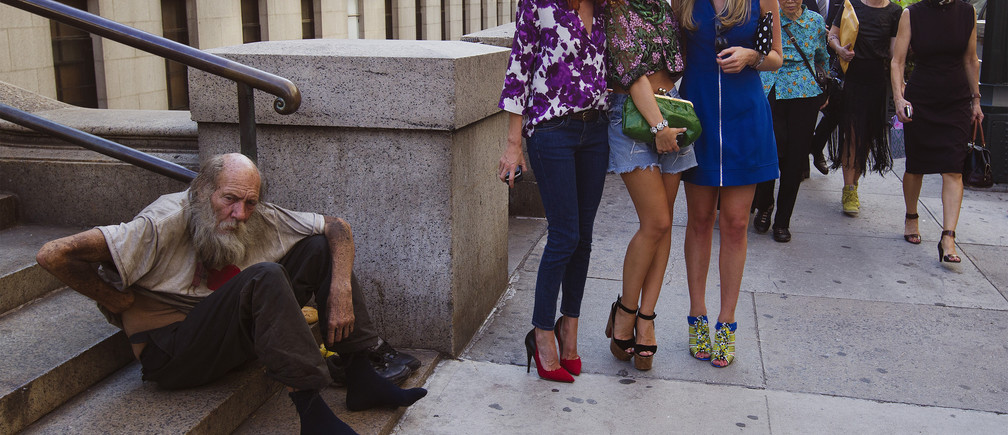 Fashionistas pose for photographs in front of a homeless man outside Moynihan Station following a showing of the Rag & Bone Spring/Summer 2013 collection during New York Fashion Week September 7, 2012. REUTERS/Lucas Jackson (UNITED STATES - Tags: FASHION SOCIETY POVERTY) - RTR37NTX
