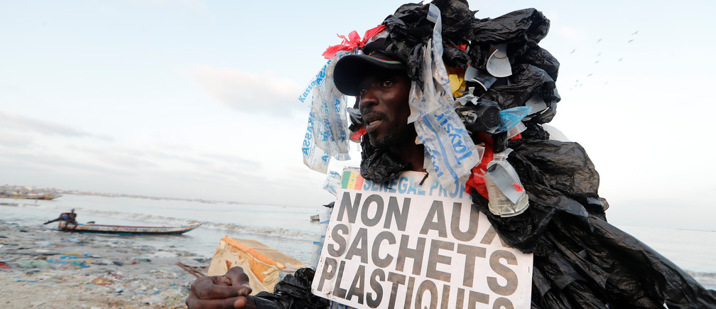 "Modou Fall, 43, head of Senegal Propre (""Clean Senegal"") Association who is covered with plastic cups and bags to raise awareness of the damage on the environment caused by plastic waste talks to residents as he walks in a fishermen port on the outskirts  of  Dakar, Senegal July 26, 2019. The placard reads: ""No to a plastic bags."" Picture taken July 26, 2019. REUTERS/Zohra Bensemra - RC1299E33270"