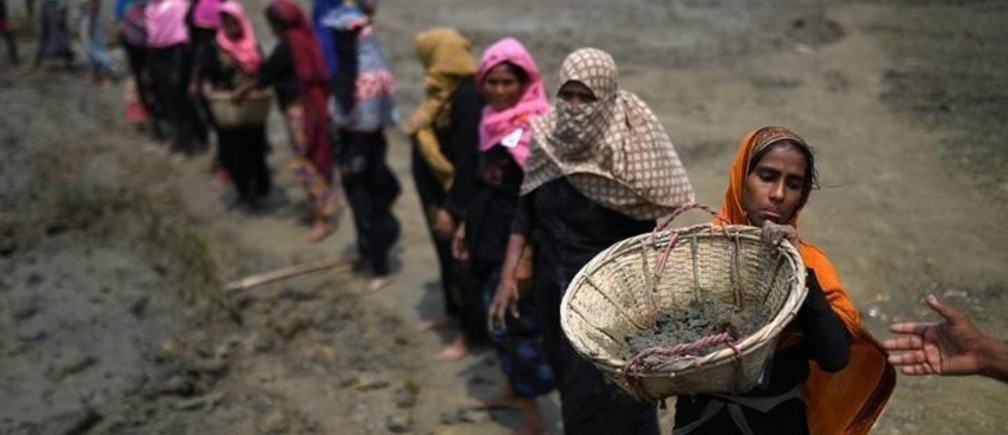 "Rohingya refugee women carry baskets of dried out mud from the riverbed to help raise the ground level of the camp in preparation for monsoon season, in Shamlapur refugee camp in Cox's Bazaar, Bangladesh, March 24, 2018. REUTERS/Clodagh Kilcoyne  SEARCH ""KILCOYNE FISHING"" FOR THIS STORY. SEARCH ""WIDER IMAGE"" FOR ALL STORIES."
