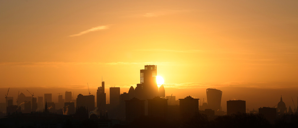 The sun is seen rising behind skyscrapers and buildings in in the City of London financial district, London, Britain, February 5, 2020.