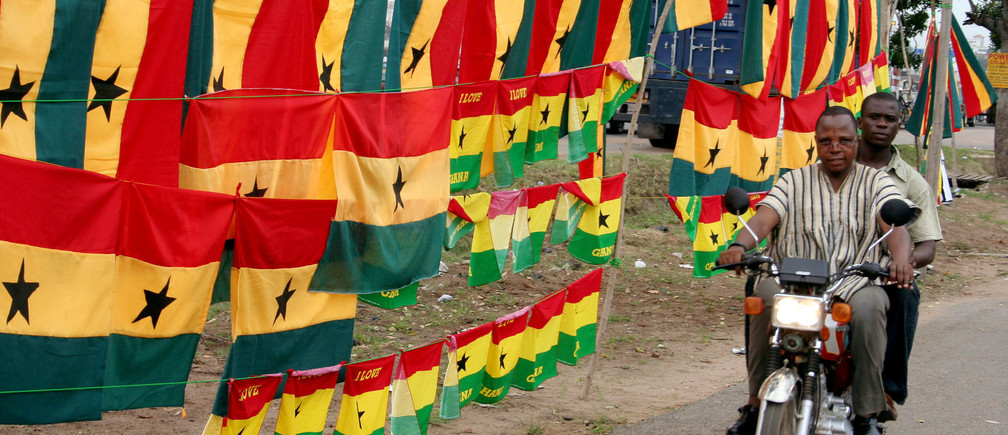 A Ghanaian motorcyclist rides past flags and soccer jerseys adorning the streets of the capital, Accra, June 4, 2006. REUTERS\Yaw Bibini