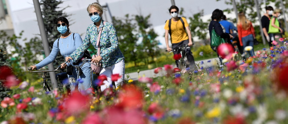 Women wearing protective masks walk with their bikes in the park in the Porta Nuova district, as Italy begins a staged end to a nationwide lockdown due to a spread of the coronavirus disease (COVID-19), in Milan, Italy May 4, 2020. REUTERS/Flavio Lo Scalzo - RC2RHG9V3TWQ